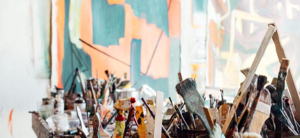 une photo de la galerie avec le mur peint en bleu, saumond, blanc mélangés et plein de pinceaux sur le 1er plan de la photo