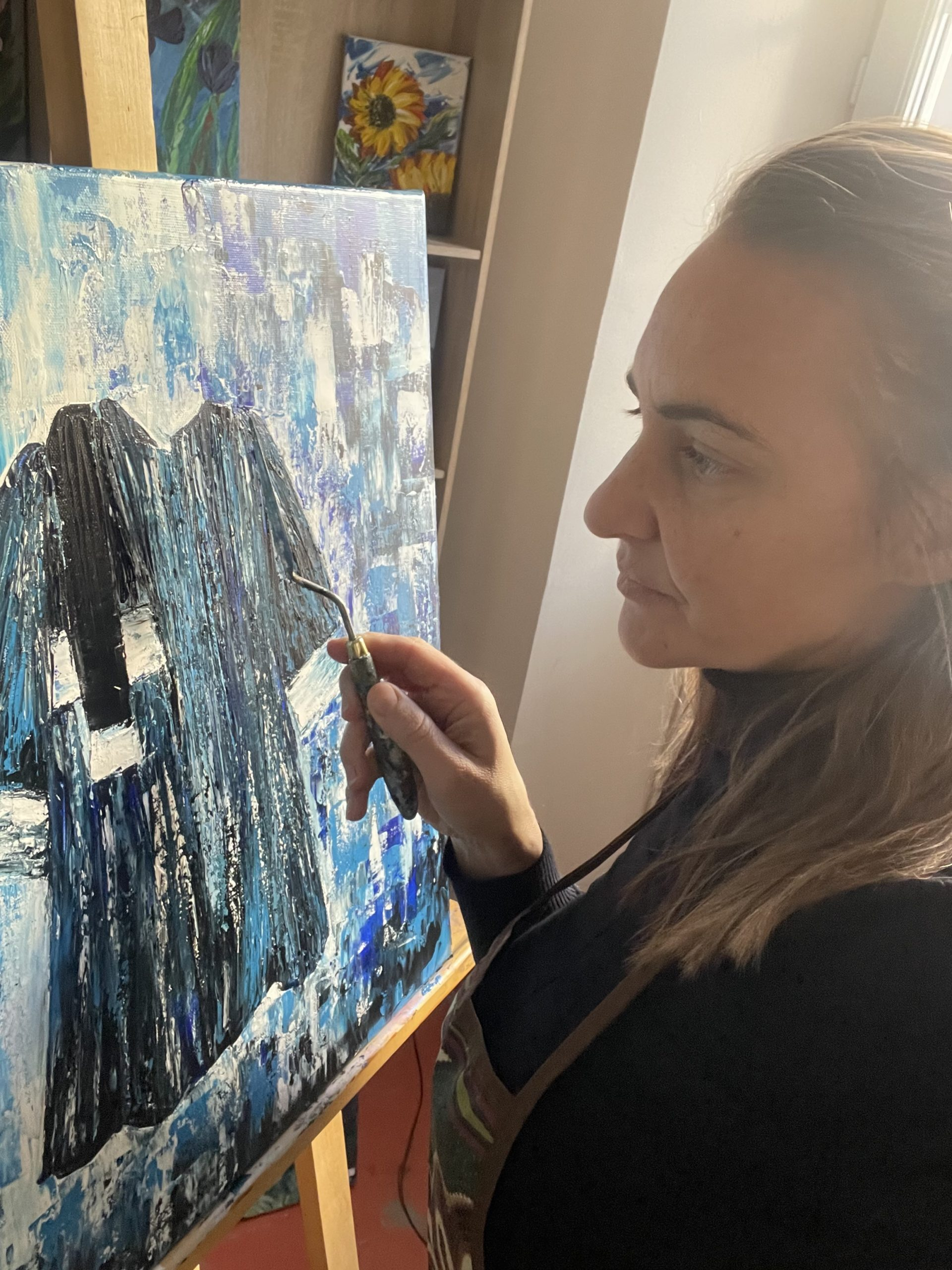 Artiste au travail - dans la page Présentation et Biographie - Inspiré de son vecu, Katarzyna Boduch, artiste entrain de réaliser au couteau un tableau